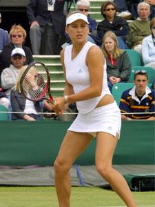 Anna Kournikova playing tennis in white