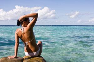 Woman in white bikini by the ocean