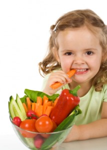 little girl eating a carrot