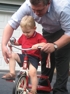 man teaching a child to ride a tricycle