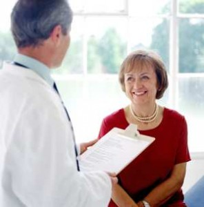 physician with clipboard with woman sitting down