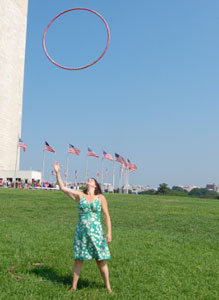 woman trowing hula hoop into the air