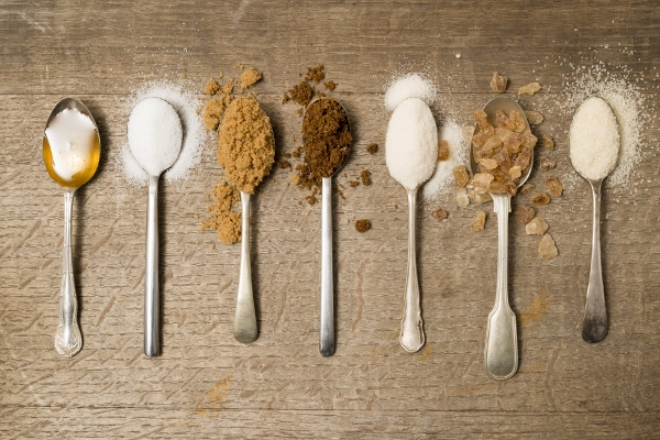 Seven teaspoons of assorted sugar spilling onto a wooden background